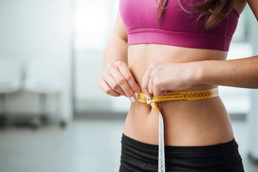 Slim woman measuring her thin waist