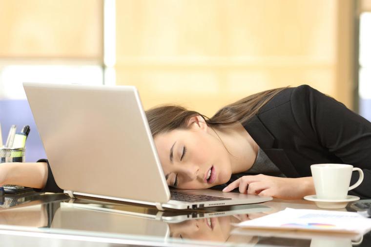Overworked businesswoman sleeping at work