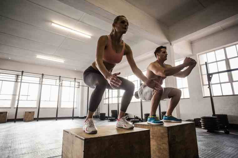 Muscular couple doing jumping squats